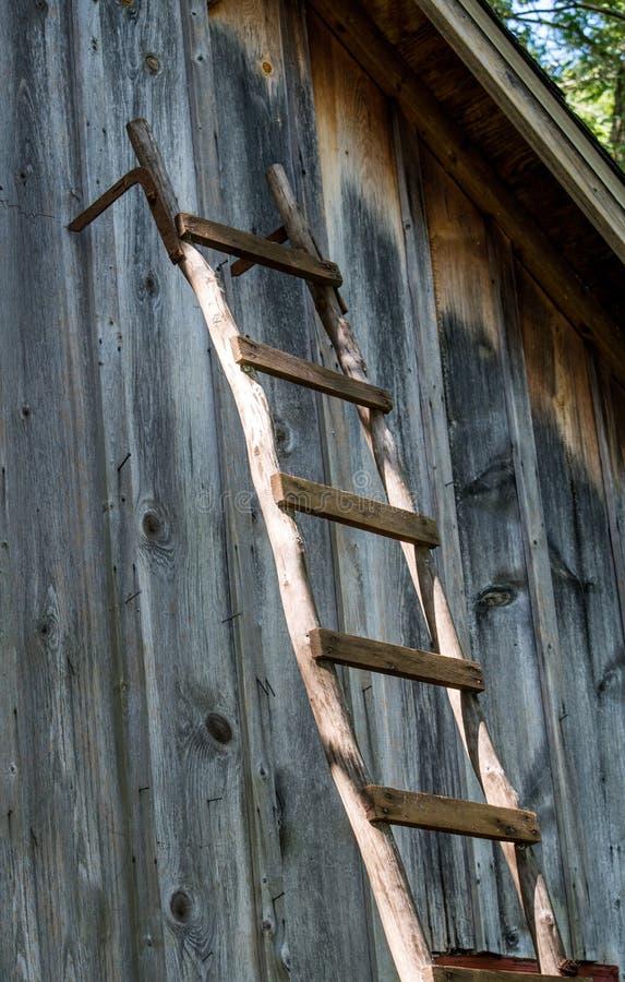 Gammal trästege mot en lantlig träladugård arkivfoton