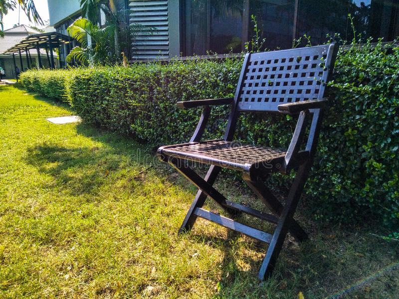 Gammal trästol i härlig trädgård arkivfoto