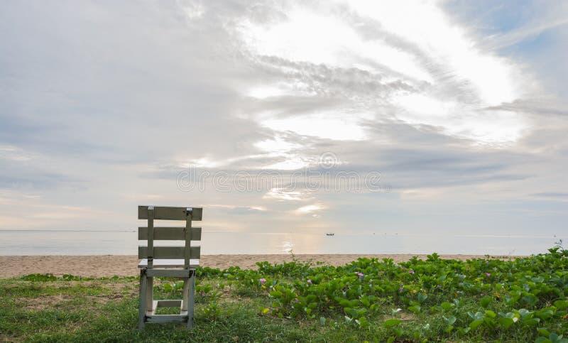 Gammal trävit stol på stranden på soluppgångtid arkivfoto