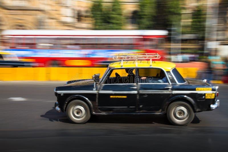 Gammal traditionell svart och guling åker taxi i rörelse som visas med att panorera för rörelsesuddighet royaltyfri foto