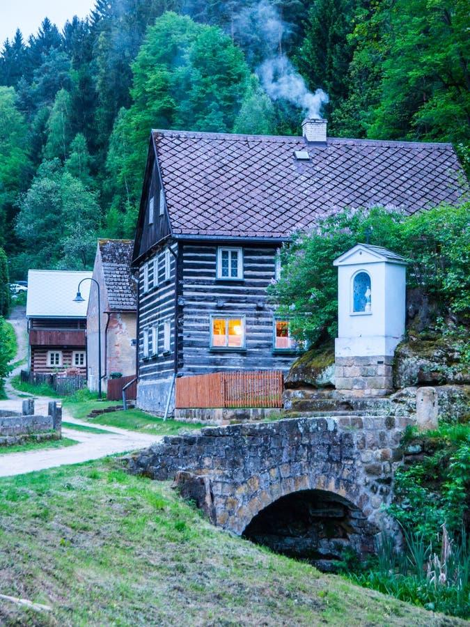 Gammal traditionell timrad stuga med romantiker med stenbron på aftontid Tjeckisk lantlig arkitektur arkivfoto