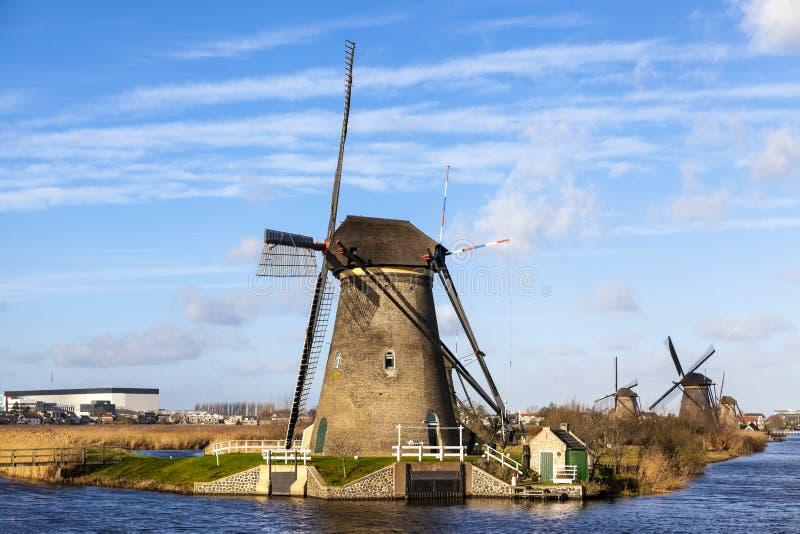Gammal traditionell väderkvarn i de holländska kanalerna Nederländerna Vit fördunklar på en blå himmel, vinden blåser arkivbilder