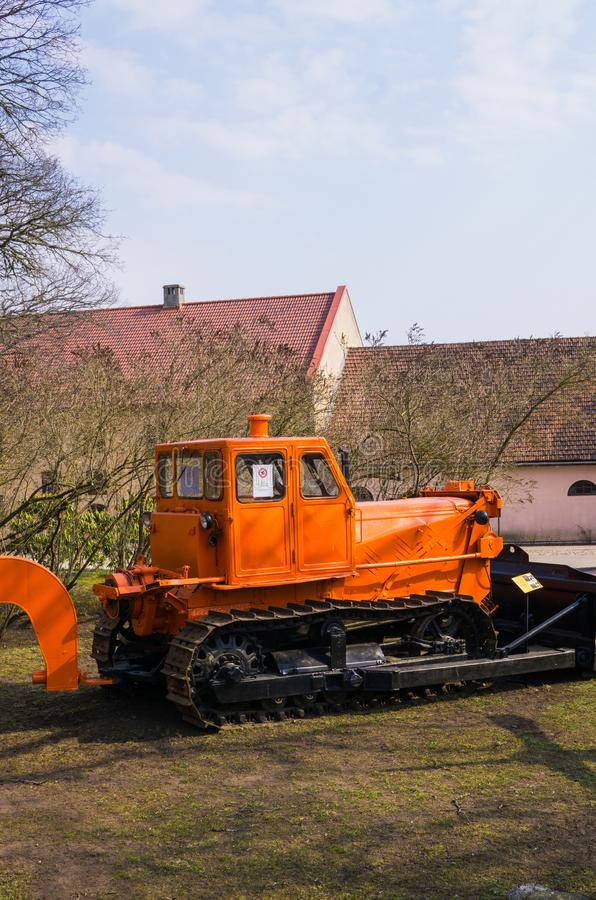 Gammal traktor f?r att b?ra ut jordbruks- arbete i ett f?lt p? en lantg?rd 7 April 2019 latvia royaltyfri foto