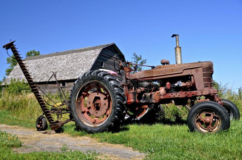 Gammal traktor- och högräsklippningsmaskin arkivbilder