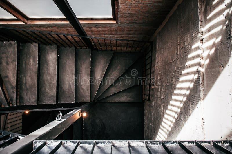 Gammal trappuppgång för industriell vind med konkret golv, svart metallH arkivfoto