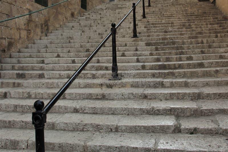 Gammal trappuppgång för sten med järnräcket i den gamla staden på ön av Malta royaltyfri foto