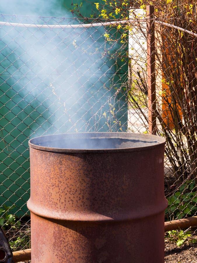 Gammal trumma som är anpassad att förbränna avfalls i det förorts- området royaltyfri fotografi