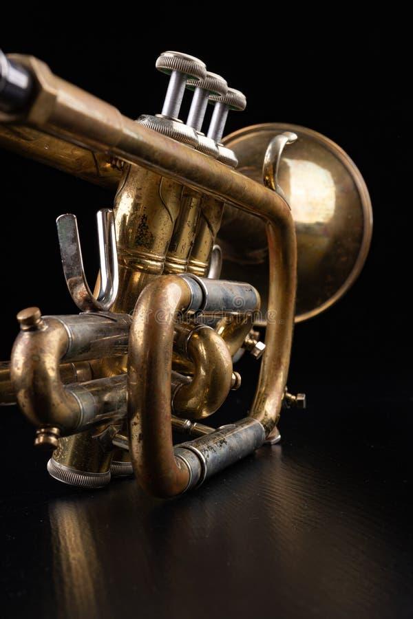 Gammal trumpet p? en m?rk tr?tabell Bl?sinstrument i den gamla stilen arkivbilder