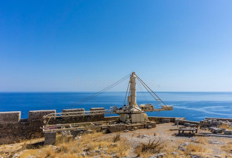 Gammal tung kran på överkanten av akropolen ovanför den forntida staden Lindos på den Rhodes ön arkivfoto