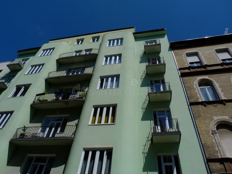 Gammal typisk mitt--löneförhöjning andelshus i Budapest i sikt för låg vinkel med små balkonger arkivfoto