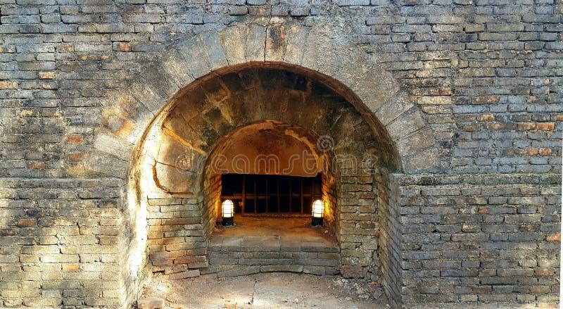 Gammal underjordisk tegelstentunnel med lampor i den thailändska templet, watumong royaltyfria bilder