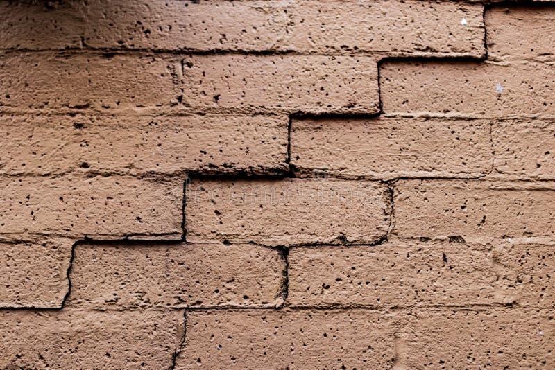 Gammal urblekt sprucken tegelstenvägg royaltyfri foto