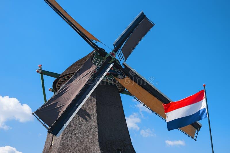 Gammal väderkvarn och flagga, Zaanse Schans, Nederländerna fotografering för bildbyråer