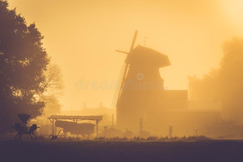 Gammal väderkvarn på guld- soluppgångljus, dimmig morgon efter regn arkivbild