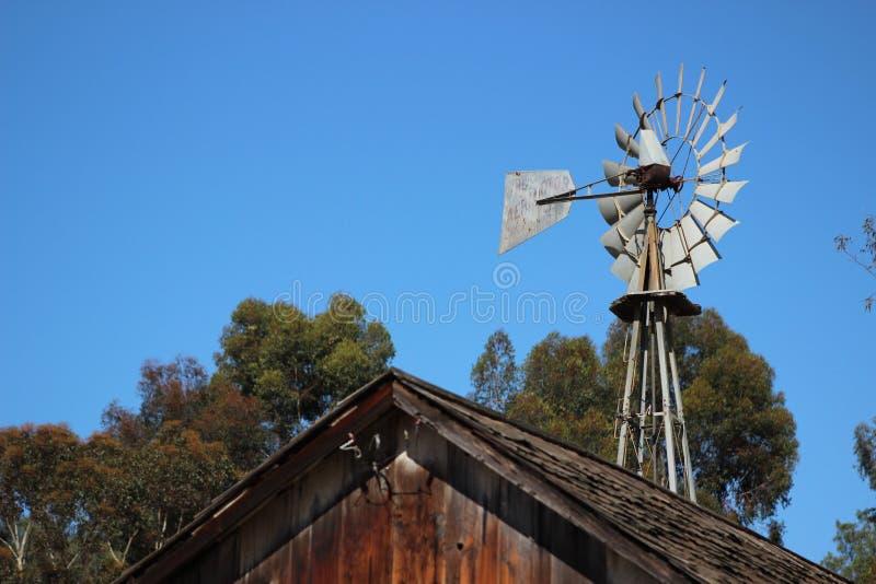 Gammal väderkvarn på historisk ranch arkivbilder