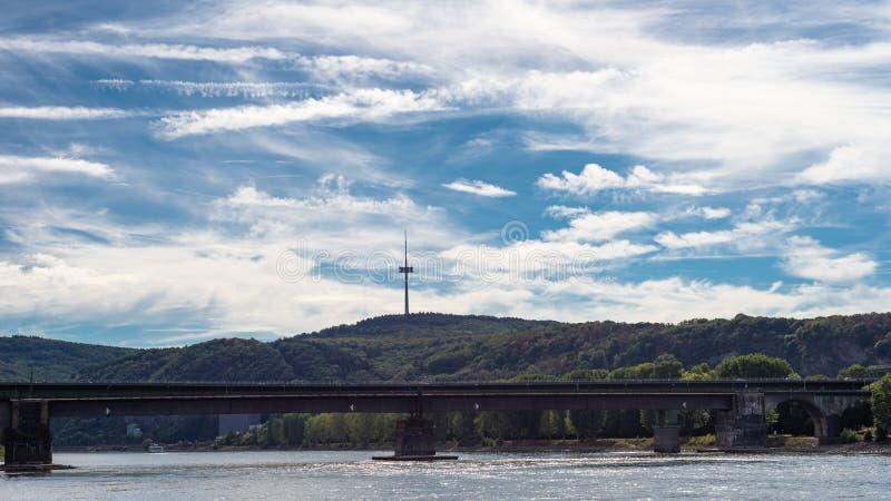 Gammal vägbro över floden i de höga kullarna för bakgrund med observationstornet, härlig blå himmel med moln royaltyfri bild