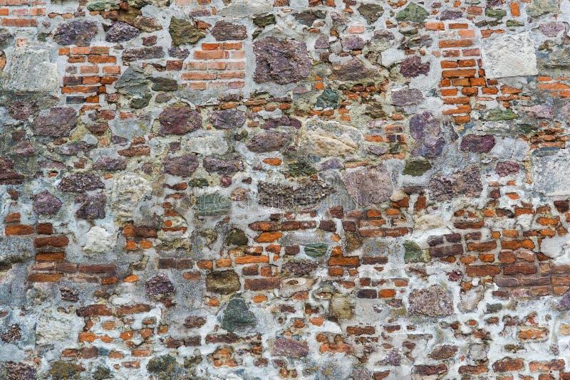 Gammal vägg av den medeltida slotten som göras av röda tegelstenar och stenen royaltyfria bilder