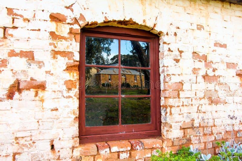 Gammal vägg, fönster och reflexion arkivfoto