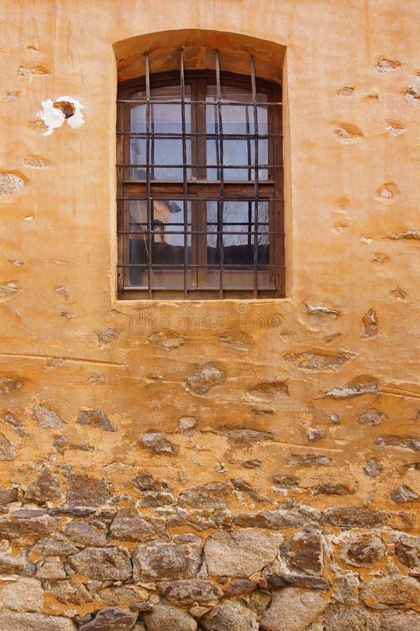 Gammal vägg för byggnadsgulingsten med fönstret och Rusty Bars arkivbilder
