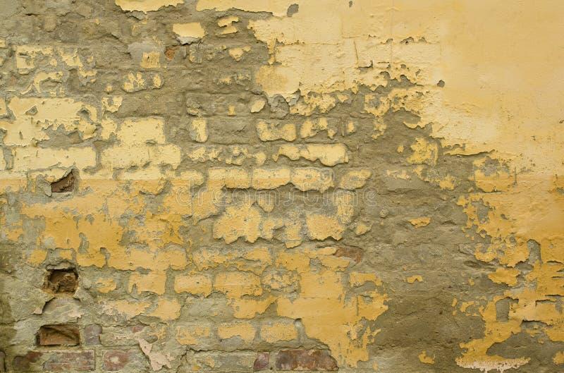 Gammal vägg för sprucken gul målarfärg royaltyfri fotografi