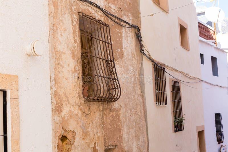 Gammal vägg med skalning av målarfärg, av skrapad tappningmurbruk och av fönster med den falska spisgallret för rostigt järn royaltyfri foto