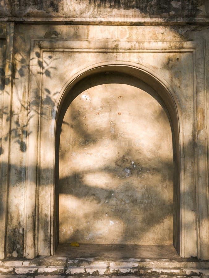 Gammal vägg med stenalkovet och fördjupning med solljus i buddistisk tempel fotografering för bildbyråer