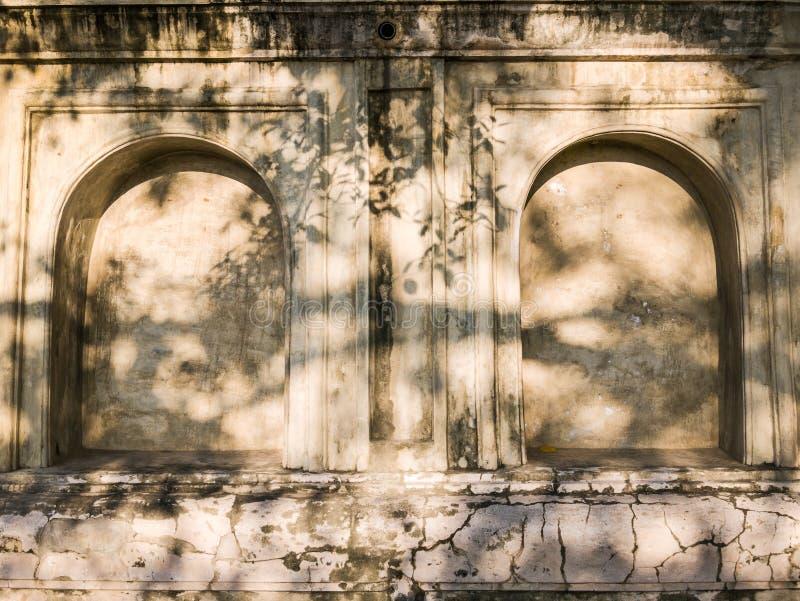 Gammal vägg med stenalkovet och fördjupning med solljus i buddistisk tempel royaltyfri fotografi