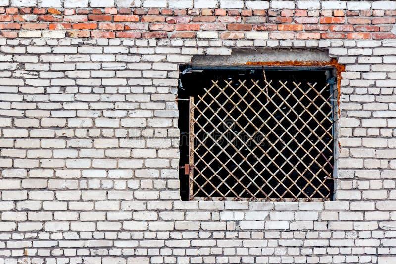 Gammal vägg som göras av vit tegelsten med ett stängt fönster arkivfoton