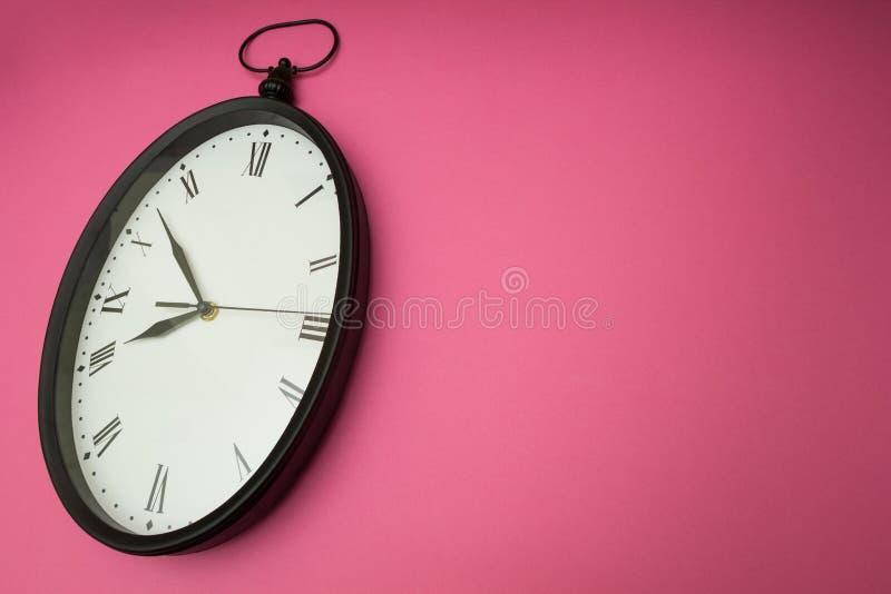 Gammal väggklocka på en rosa bakgrund arkivfoton