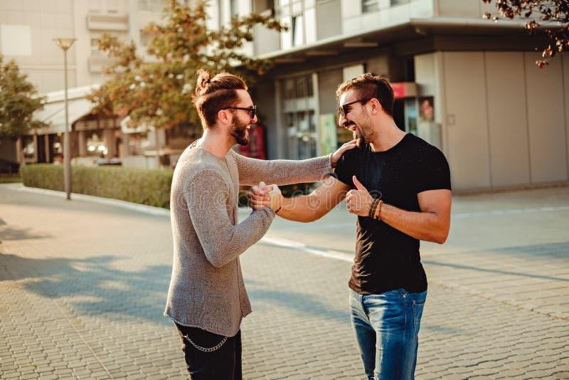 Gammal vänmöte och skratta, medan skaka händer arkivfoton