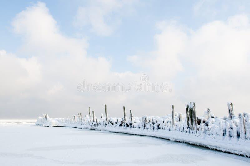 Gammal vågbrytare som täckas i snö arkivbild