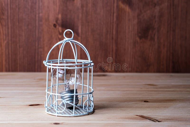 Gammal vanlig glödande lampa i dekorativ bur på trätabellen royaltyfri foto
