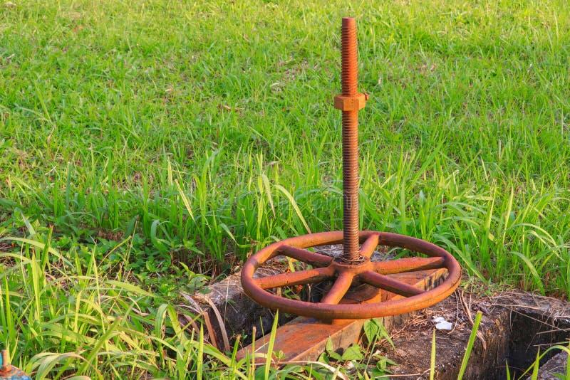 Gammal vattenventil och rostigt på gräset arkivbilder