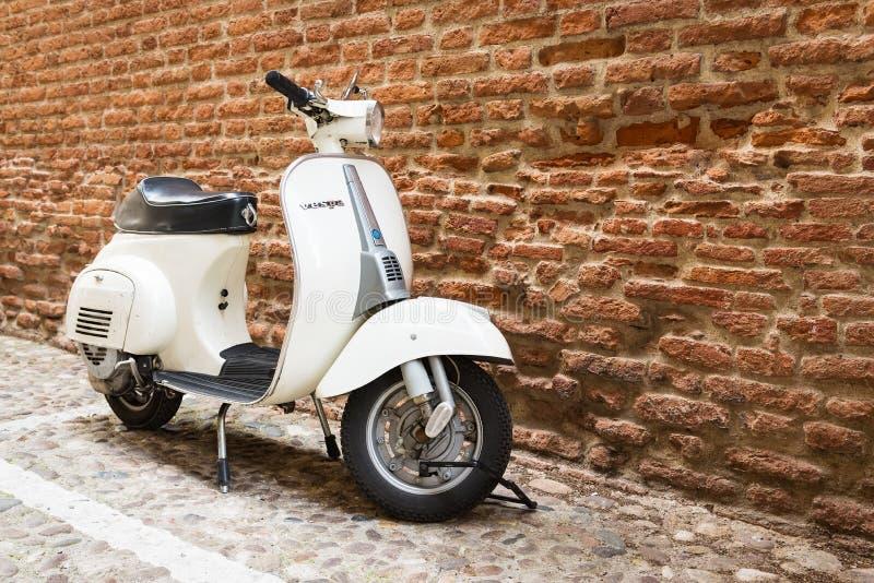 Gammal Vespa som parkeras på den gamla gatan i Verona royaltyfri foto
