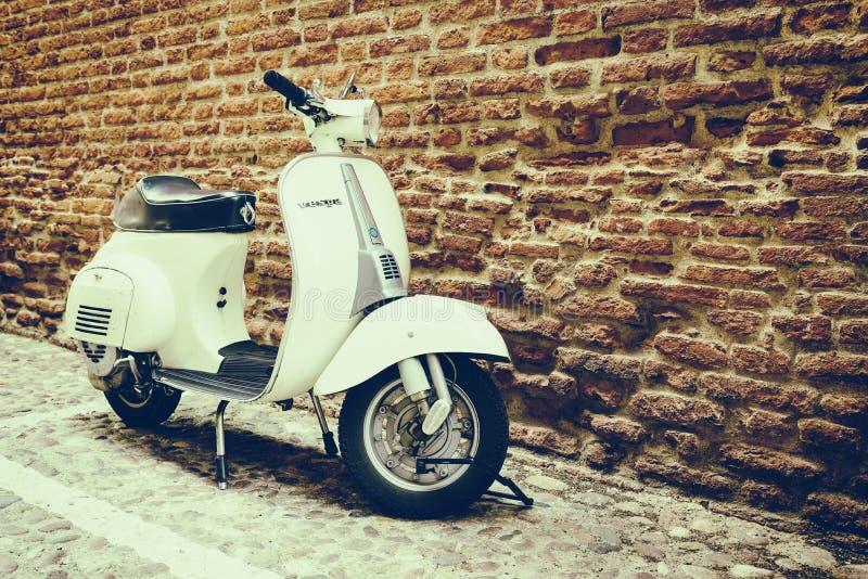 Gammal Vespa som parkeras på den gamla gatan i Verona arkivfoto