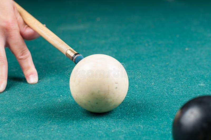 Gammal vit billiardboll och pinne på en grön tabell billiardbollar som isoleras på en grön bakgrund royaltyfri foto