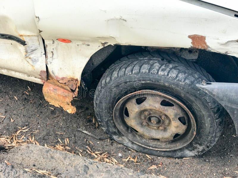 Gammal vit rostig bruten bil av kadavret med fällda ned punkterade hjul med skrapakorrosion och en sönderriven-av stötdämpare med royaltyfri fotografi