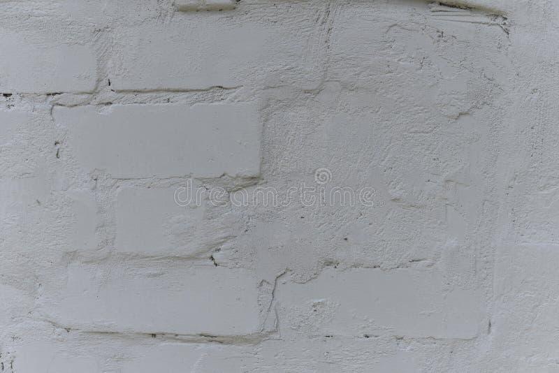 Gammal vit skapade ungefärligt den målade tegelstenväggen med vit målarfärg, slut upp, kopieringsutrymme arkivfoto