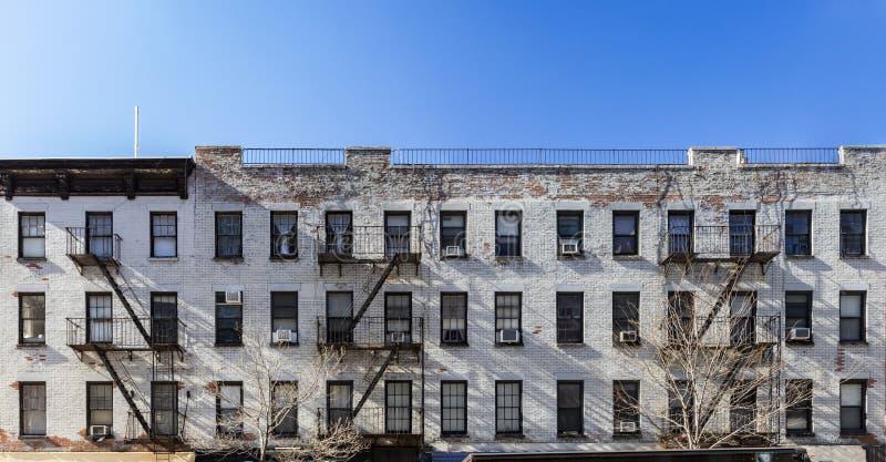 Gammal vit tegelstenhyreshus med fönster och brandflykter i New York City royaltyfri foto