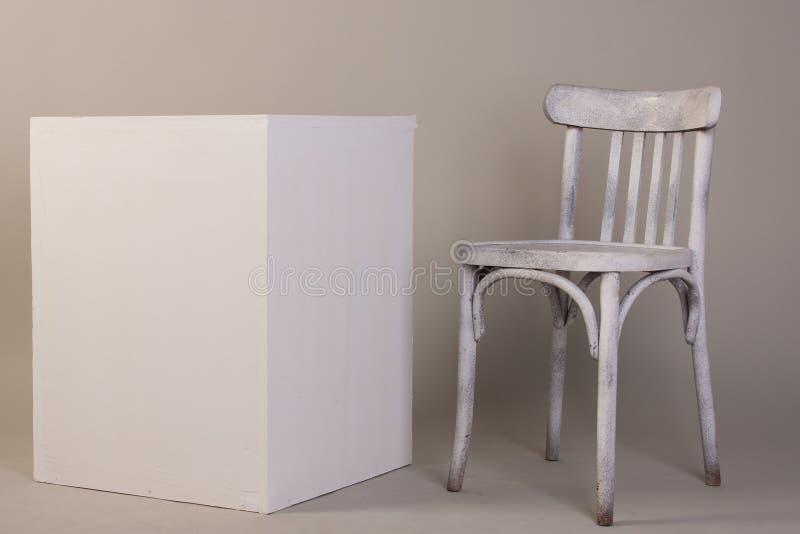 Gammal vit trästol och kub som isoleras på en grå bakgrund fotografering för bildbyråer
