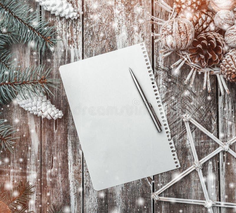 Gammal wood bakgrund, grönt granträd med vita kottar, en korg av kottar och valnötter och en dekorativ stjärna, bokstav till jult fotografering för bildbyråer