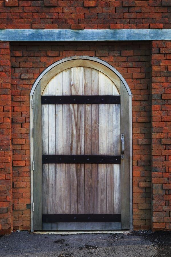 Gammal wood ladugårddörr och tegelstenvägg fotografering för bildbyråer
