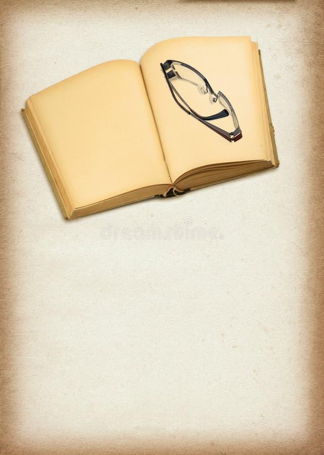 Gammala öppna bok och exponeringsglas arkivfoton