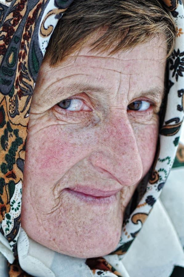 Gammalare kvinna med scarfen arkivfoton