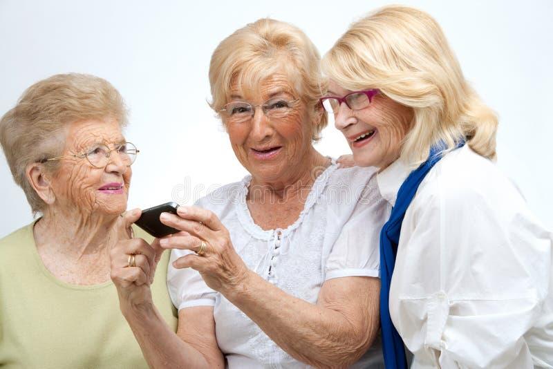 Gammalare kvinnligvänner med den mobila apparaten. royaltyfria foton