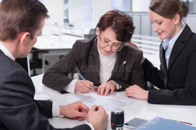 Gammalare kvinna som undertecknar ett dokument royaltyfria bilder