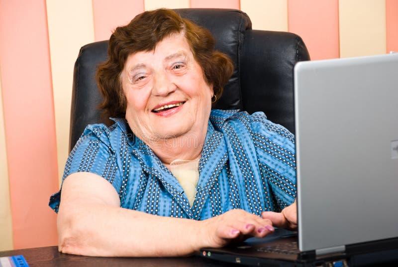 gammalare lycklig bärbar dator för affär genom att använda kvinnan royaltyfri fotografi