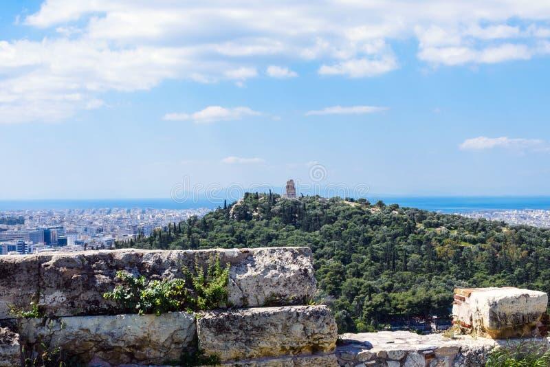 Gammalgrekiska fördärvar, fördärvar under frodigt grönt gräs acropolis athens greece eautiful sikt av huvudstaden av Grekland - A royaltyfri fotografi