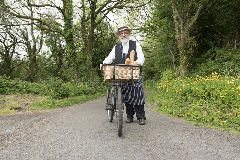 Gammalmodig leveransman på en cykel arkivfoton
