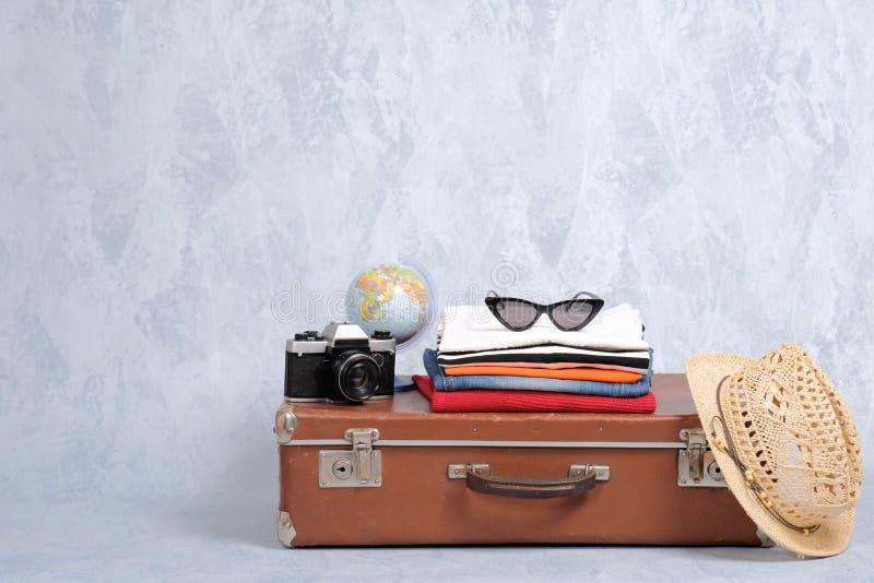 Gammalmodig loppresväska med sommartillbehör: exponeringsglas packe av att bekläda, retro fotokamera, sugrörstrandhatt på grå bak arkivbilder